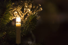 Christmas toy candle in front of a Christmas tree with sparkling lights Stock Photography