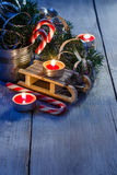 Christmas toy and candy canes. Christmas toy sledge, candy canes, candles and spruce branches on a white background Stock Images