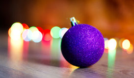 Christmas toy on the Christmas tree. Purple round wooden toy on the floor, on a background bokeh Royalty Free Stock Images