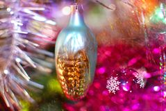 Christmas toy in the form of corn on a background of a bright sparkling multi-colored tinsel