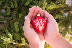 Christmas toy in form of red heart in hands Royalty Free Stock Photo