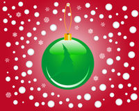 Christmas toy. Green Christmas toy on a red background with balls and snowflakes Royalty Free Stock Photography
