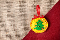 Christmas toy. Christmas handmade toy with tree from felt on sackcloth background royalty free stock images