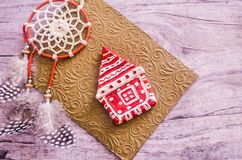 Christmas toy-house and dreamcatcher on the background of a golden embossed envelope royalty free stock photo