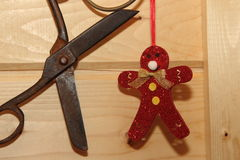 Christmas toy man red and vintage scissors. On a wooden wall background Stock Photo