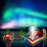 Christmas toy with Northern Lights. Illustrated red fire rescue truck toy in box with ornaments and Northern Lights in starry skies with copy space Royalty Free Stock Photos