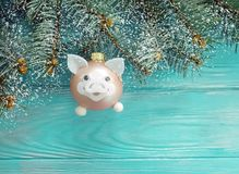 Christmas toy pig card on a wooden background, snow, tree branch. Christmas toy pig on a wooden background, snow tree branch card stock photo