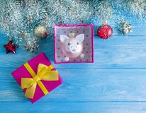 Christmas toy pig card Christmas tree gift box bow a wooden background, snow, tree branch. Christmas toy pig on a wooden background, snow tree branch Christmas royalty free stock photo