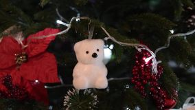 Christmas toy polar bear hanging on the Christmas tree and flickering garland stock footage