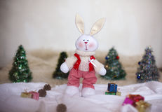 Christmas toy rabbit on background trees Royalty Free Stock Image
