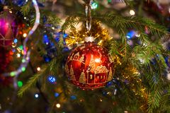 Christmas toy red glass ball, painted with gold, hangs on the fir tree. Colorful Christmas background. Christmas toy red glass ball, painted with gold, hangs on stock photo
