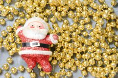 Christmas toy Santa Claus on golden beads. stock photography
