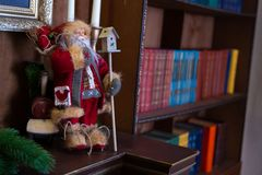 Christmas toy Santa Claus is on the shelf in the library. Background bookshelf bokeh. New year`s interior. royalty free stock photos