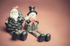 Christmas toy of Santa Claus and snowman at red background Stock Images