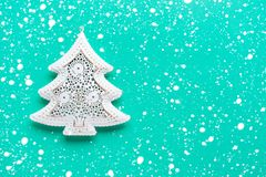 Christmas toy in the shape of a Christmas tree on a green background. Free space on the right. Snowflakes effect royalty free stock photo