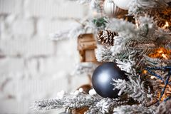 Christmas toy silver ball hanging on a Christmas tree on the background of a white brick wall stock images