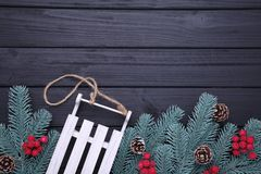 Christmas toy sledge with fir-tree branch on a black background. Christmas decoration royalty free stock photo