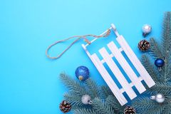 Christmas toy sledge with fir-tree branch on a blue background stock images