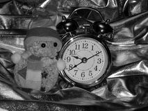 Christmas toy with a snowman and an alarm clock on a black and white image. Close-up royalty free stock photos