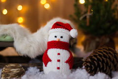 Christmas Toy Snowman and cones under the tree. Christmas Toy Snowman and cones under the tree on the background of garlands Stock Photography
