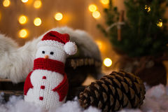Christmas Toy Snowman and cones under the tree. Close-up. Christmas Toy Snowman and cones under the tree on the background of garlands. Close-up Royalty Free Stock Images