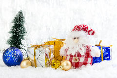 Christmas toy snowman with gifts on snowy background Stock Images