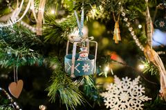 New year toy snowman hanging on a decorated Christmas tree stock images