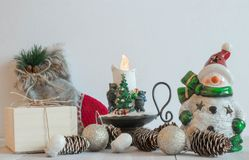 Christmas toy snowman on a light background with decorative candles. Christmas horizontal composition. Christmas decorations. New stock image