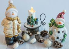 Snowman decorative toy on a light background with decorative candles and cones. Christmas horizontal composition. Christmas stock image