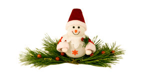 Christmas toy snowman on a pine branches. Christmas toy snowman in a red cap and a red fur coat sits on a decorated green pine branch. It has nice and frendly Royalty Free Stock Photo