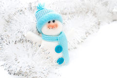 Christmas toy Snowman and tinsel on a white background Royalty Free Stock Image
