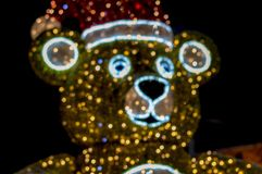 Christmas toy - Statue. Bear. Made of garlands and tinsel, of different colors. It stands near the tree fir. Decoration. stock images