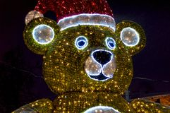 Christmas toy - Statue. Bear. Made of garlands and tinsel, of different colors. It stands near the tree fir. Decoration. stock image