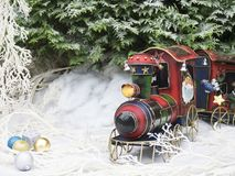 Christmas toy steam train in the winter forest. In the background the snow-covered coniferous tree branches. Land in the snow. Snow Christmas tree decorations Royalty Free Stock Photography