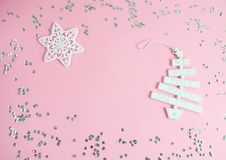 Christmas toy with text We wish you a Merry Christmas in pastel pink background with silver glitter, party concept. Top view royalty free stock images