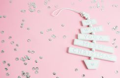 Christmas toy with text We wish you a Merry Christmas in pastel pink background with silver glitter, party concept. Top view royalty free stock photo
