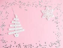 Christmas toy with text We wish you a Merry Christmas in pastel pink background with silver glitter, party concept. Top view stock photography