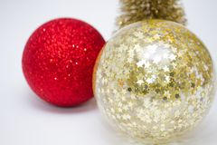Christmas toy, two shiny balls of red and golden and golden tree. New Year. On a gray background royalty free stock photography