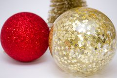 Christmas toy, two shiny balls of red and golden and golden tree. New Year. On a gray background royalty free stock image