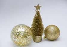 A Christmas toy, two shiny golden balls and a golden Christmas tree. New Year. On a gray background royalty free stock images