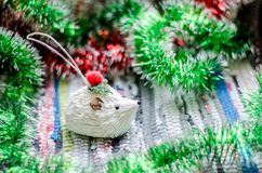 Christmas toy white hedgehog with green and red garlands closeup. royalty free stock image