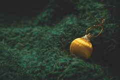 Christmas toy. Yellow Christmas ball on a soft green background. Christmas holiday celebration concept stock images