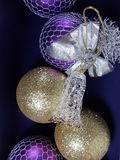 Christmas toys background. Christms glittering balls and a glass bell  on the velvet paper background Stock Photo