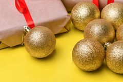Christmas toys balls of gold color with sequins and a gift box with a Kraft wrapper and a red ribbon lie on a background. Christmas toys balls of gold color with stock images