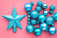 Christmas toys. Blue balls and stars on pink background top view Stock Image