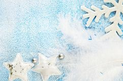 Christmas toys on a blue and white snowy background. Stars, snowflakes and feathers. New year and Christmas toys blue and white. Snowflakes and stars on a snowy Royalty Free Stock Image
