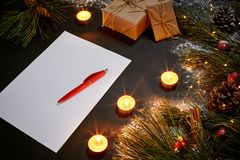 Christmas toys, burning candles and notebook lying near green spruce branch on black background top view. Space for text Stock Photos