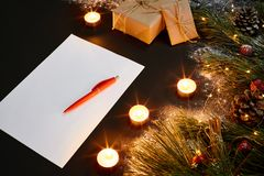 Christmas toys, burning candles and notebook lying near green spruce branch on black background top view. Space for text Stock Image
