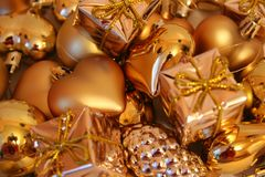 Christmas toys of different form of gold color, bright background. royalty free stock photography