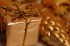 Christmas toys of different form of gold color, bright background. stock photos